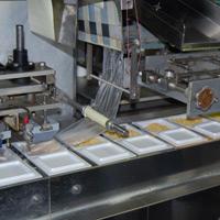 盛り込まれた納豆は、機械でパックされます。